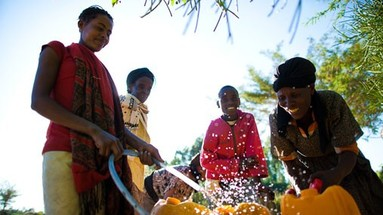 Ethiopian women using new water pumpt to fill containers.