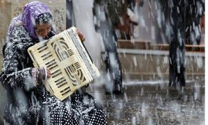 Woman plays accordion on street in snow in Buxton, U.K.